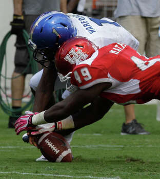 UH's Derrick Mathews recovers a fumble by Memphis' Marquis Warford, one of four turnovers forced by the Cougars' defense Saturday. Photo: Melissa Phillip, Staff / © 2013  Houston Chronicle