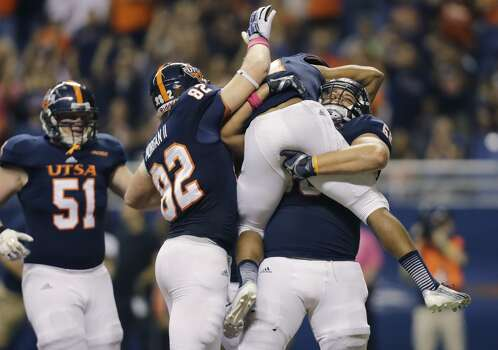 UTSA's Cody Harris, right, picks up teammate David Glasco II who scored a touchdown against Rice during the first half of an NCAA college football game on Saturday, Oct. 12, 2013, in San Antonio. UTSA's Payton Rion (51) and David Morgan II (82) also celebrate. (AP Photo/Eric Gay) Photo: Eric Gay, Associated Press