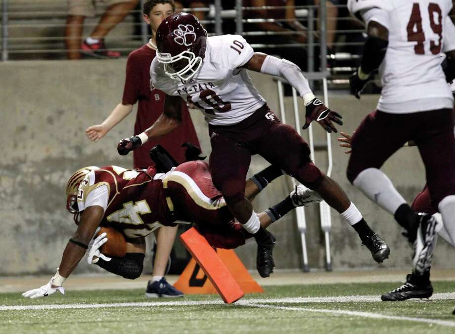 Cy-Woods' Samuel Stewart, left, scores a touchdown past Cy-Fair's Brandon Richmond during the second half of a high school football game, Saturday, October 12, 2013 at Berry Center in Cypress. Photo: Eric Christian Smith, For The Chronicle