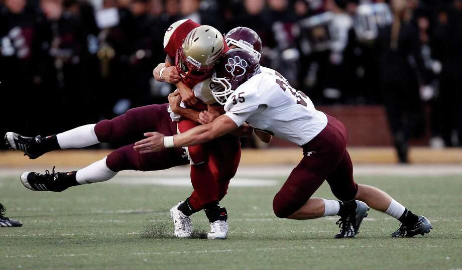 Cy-Woods' Nick Hooper, left, is tackled by Cy-Fair's Austin Scheaffer (35) and James Kohlschmidt during the first half of a high school football game, Saturday, October 12, 2013 at Berry Center in Cypress. Photo: Eric Christian Smith, For The Chronicle