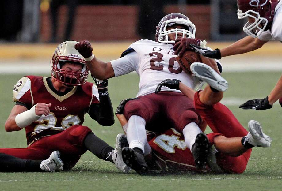 Cy-Fair's Dillon Birden (20) is tackled by Cy-Woods' Hector Larios during the first half of a high school football game, Saturday, October 12, 2013 at Berry Center in Cypress. Photo: Eric Christian Smith, For The Chronicle