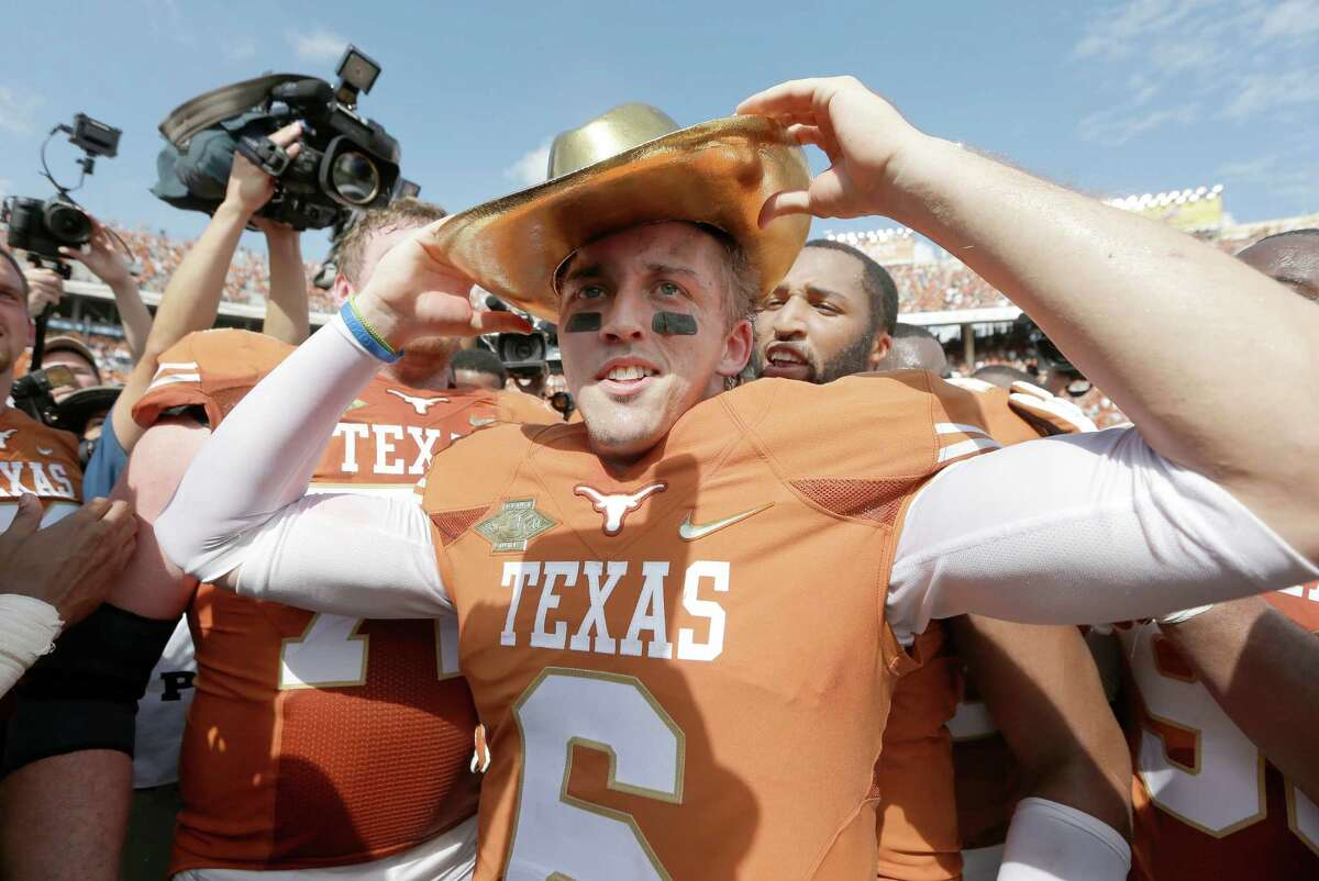 Texas quarterback Case McCoy likes the fit of the Golden Hat trophy.
