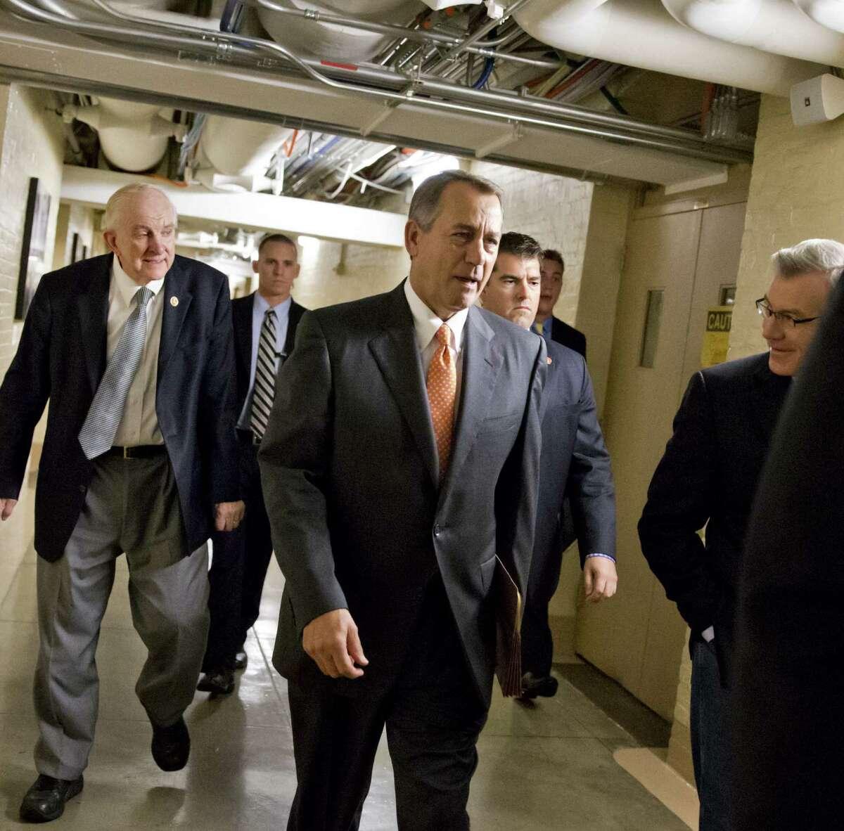 Speaker John Boehner walks with fellow Republicans on the same day House GOP talks with President Barack Obama fail.