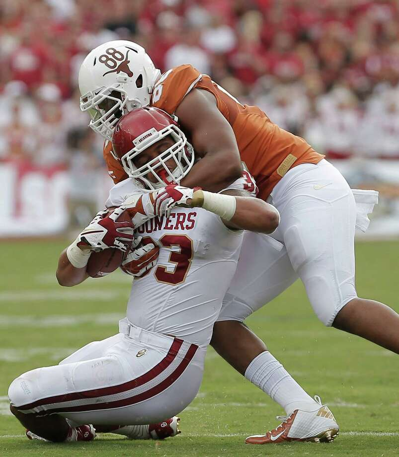 A stout defensive effort by Texas included a stop of Oklahoma fullback Trey Millard by Longhorns defensive end Cedric Reed. Photo: Brandon Wade, FRE / FR168019 AP
