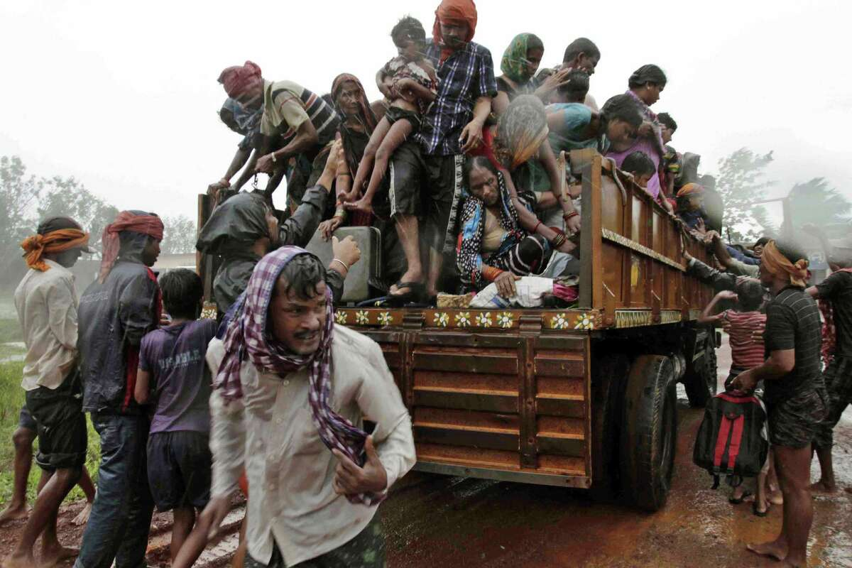 Evacuated Indian villagers get down from a truck at a relief camp as it rains near Berhampur after a cyclone not as fierce as feared reaches landfall. U.S. forecasts had been more dire than India's.