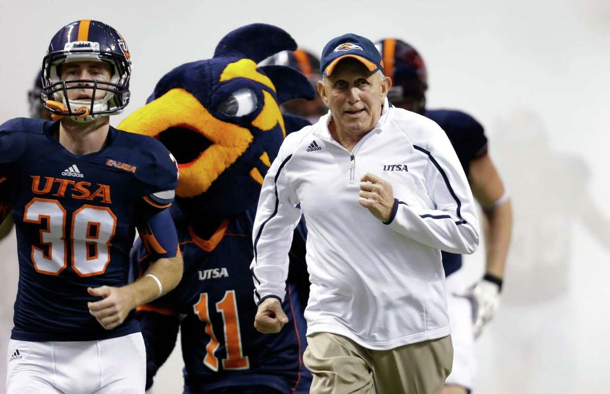 Texas San Antonio coach Larry Coker, right, runs onto the field with his team prior to an NCAA college football game, Saturday, Sept. 28, 2013, in San Antonio. (AP Photo/Eric Gay)