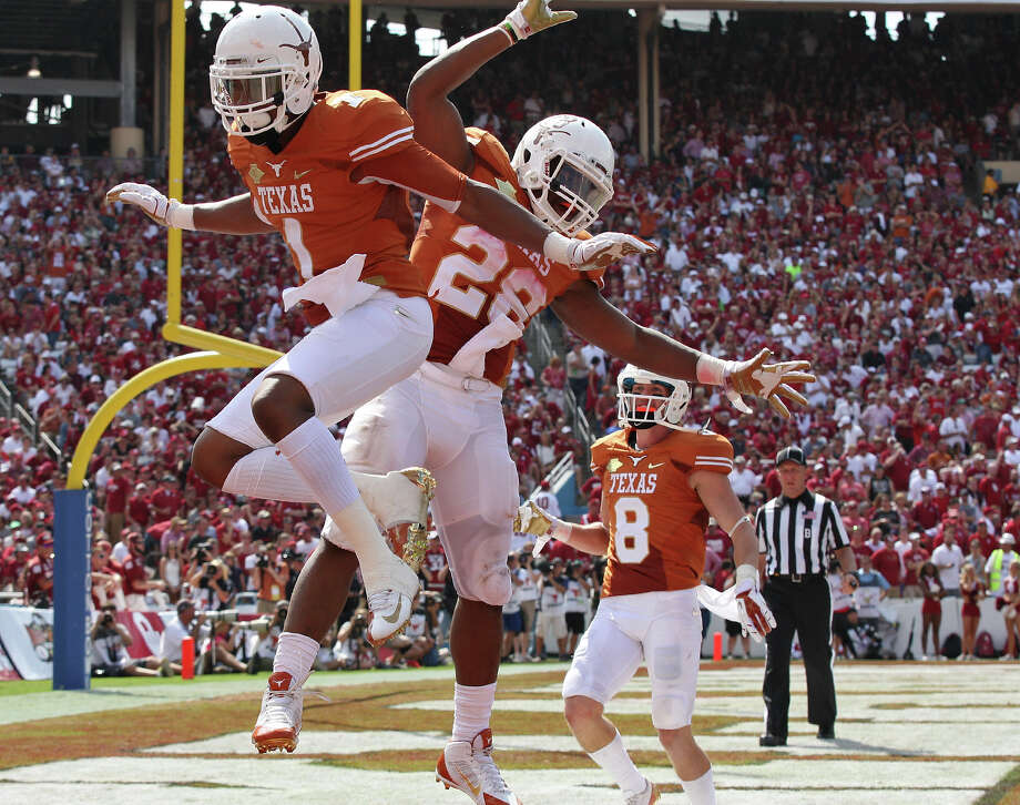 Texas Longhorns' Mike Davis (from left), Malcolm Brown, and Jaxon Shipley celebrate after Davis scored a touchdown on a pass play against the Oklahoma Sooners during second half action of the Red River Rivalry held Saturday Oct. 12, 2013 at Cotton Bowl Stadium in Dallas, Tx. The Longhorns won 36-20. Photo: San Antonio Express-News / © 2013 San Antonio Express-News