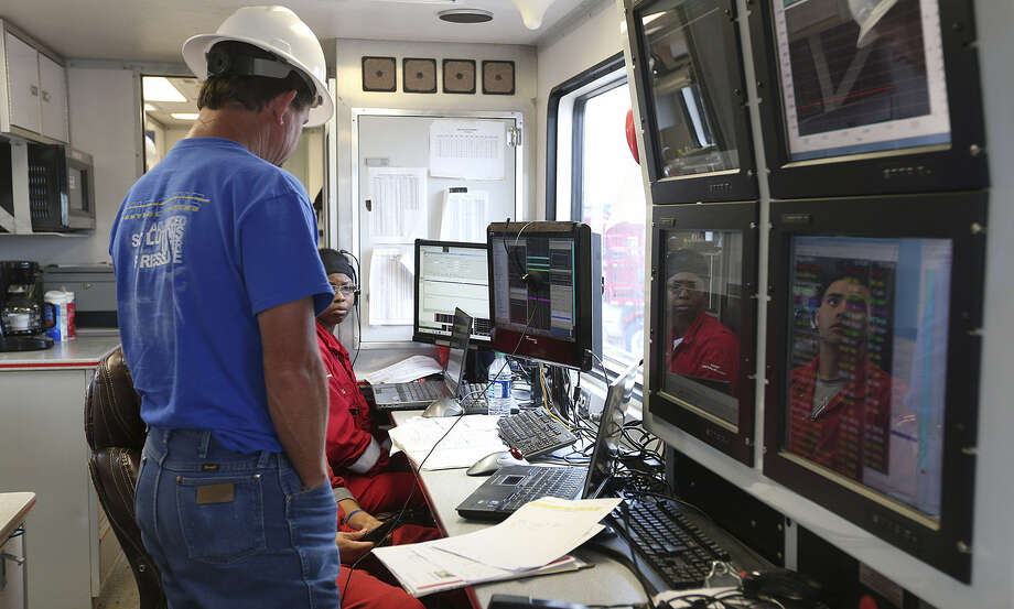 The faces of engineers Audrea Holmes and Paul Aleman are reflected on computer screens as they update Russell Musgrove of R.W. Dirks Petroleum during a hydraulic fracturing job in Jim Wells County. Photo: Photos By Jerry Lara / San Antonio Express-News