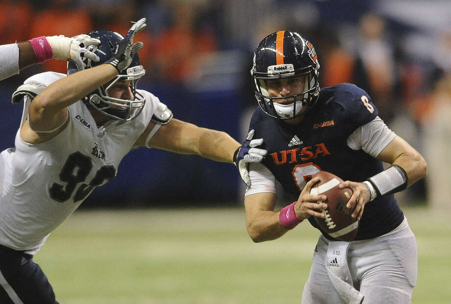 Eric Soza, trying to evade Rice's Cody Bauer, led UTSA on fourth-quarter scoring drives of 78 and 76 yards in the loss. Photo: Billy Calzada / San Antonio Express-News