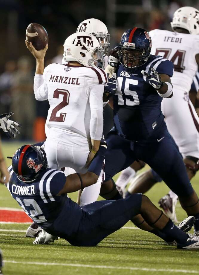Texas A&M quarterback Johnny Manziel (2) is tackled by Mississippi defensive back Tony Conner (12) as he grounds the ball in the first half of their NCAA college football game at Vaught-Hemingway Stadium in Oxford, Miss., Saturday, Oct. 12, 2013. Manziel was penalized for grounding the ball. (AP Photo/Rogelio V. Solis) Photo: Rogelio V. Solis, Associated Press