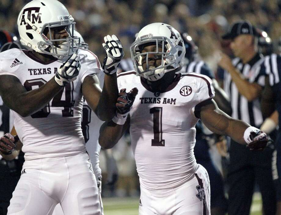 Texas A&M running back Ben Malena (1) and wide receiver Malcome Kennedy (84) celebrate Malena's touchdown against Mississippi in the first half of their NCAA college football game at Vaught-Hemingway Stadium in Oxford, Miss., Saturday, Oct. 12, 2013. (AP Photo/Rogelio V. Solis) Photo: Rogelio V. Solis, Associated Press