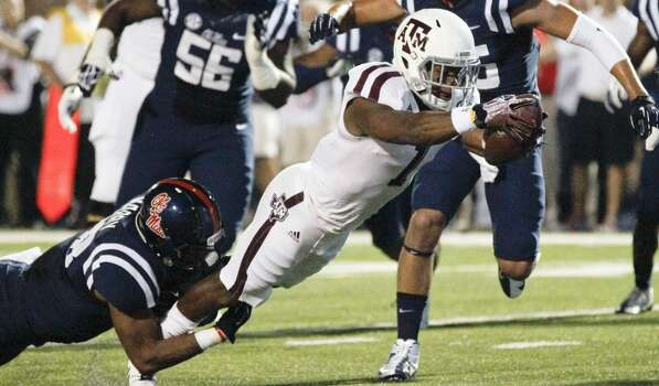 Texas A&M running back Ben Malena (1) lunges forward through the hands of Mississippi linebacker Mike Marry (38) for a seven-yard touchdown run in the first half of their NCAA college football game at Vaught-Hemingway Stadium in Oxford, Miss., Saturday, Oct. 12, 2013. (AP Photo/Rogelio V. Solis) Photo: Rogelio V. Solis, Associated Press