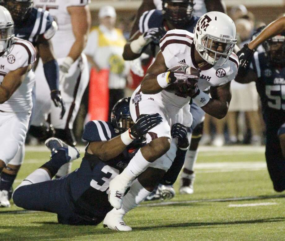 Texas A&M running back Ben Malena (1) runs through the hands of a Mississippi defender for a 7-yard touchdown run in the first half of their NCAA college football game at Vaught-Hemingway Stadium in Oxford, Miss., Saturday, Oct. 12, 2013. (AP Photo/Rogelio V. Solis) Photo: Rogelio V. Solis, Associated Press