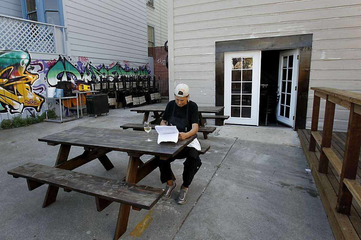 Restaurant manager Melissa Garbiras works on her supply purchases outside in the area of the proposed bocce ball courts Thursday October 10, 2013 in San Francisco, Calif. Rustica restaurant near 24th and Mission is trying to get approval for putting bocce ball courts in an area behind the restaurant.