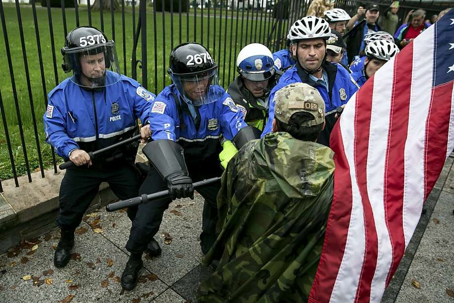 Police prevent a protester from nearing the fence outside the White House in Washington. Demonstrators were protesting the closure of public memorials. Photo: Drew Angerer, New York Times