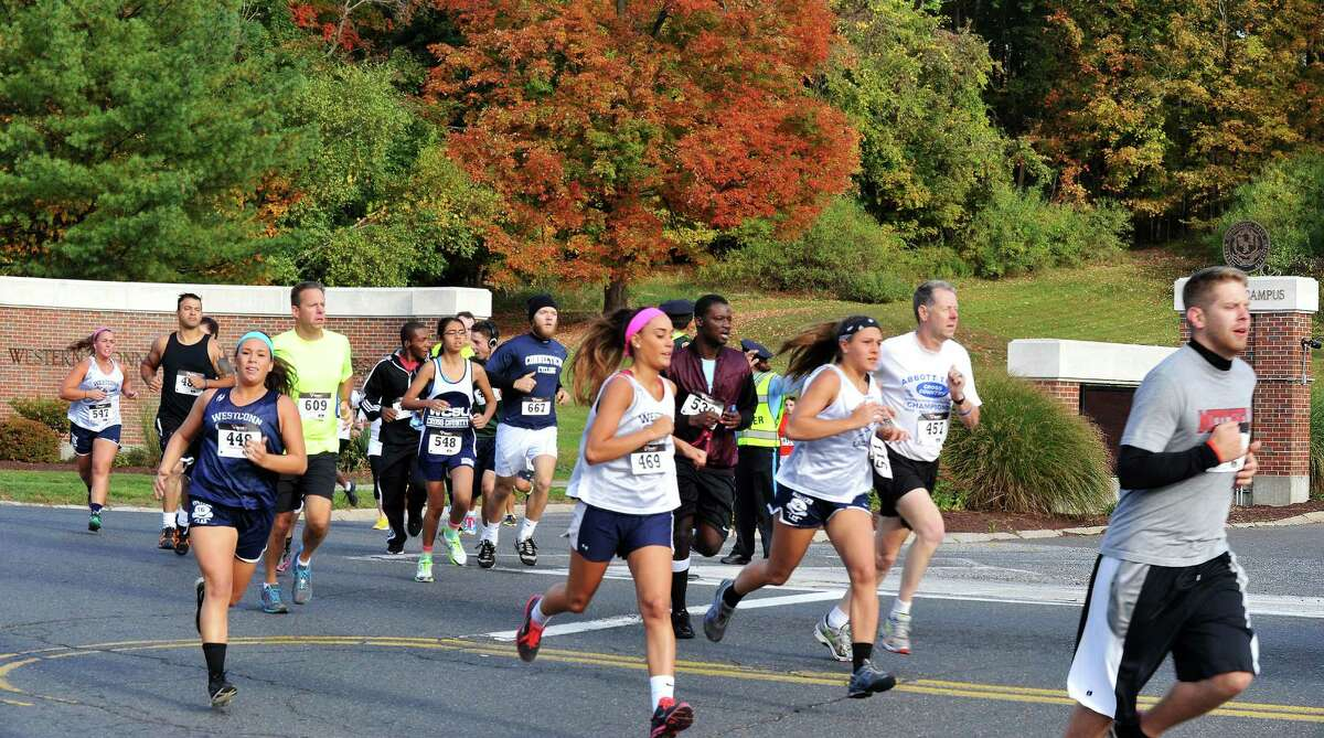 Runners leave Western Connecticut State University's westside campus at the start of the Campus-to-Campus 5K roadrace in Danbury, Conn. Sunday, Oct. 13, 2013. The 3.1 mile race ends at the midtowm campus and kicks off the university's homecomming week events.
