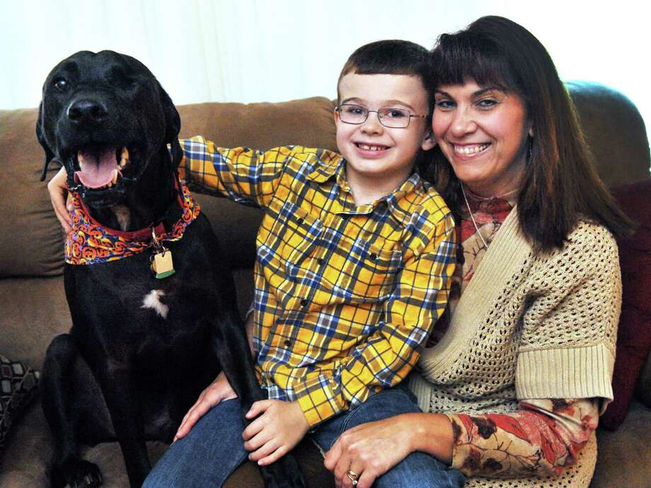 Barbie Mable holds her son, Gregory, 7, in their New Fairfield, Conn., home Sunday, Oct. 13, 2013. Gregory received a corneal transplant from an organ donor. With them is Sky, a rescue dog with one eye, who bonded with Gregory during his recovery. Photo: Michael Duffy / The News-Times