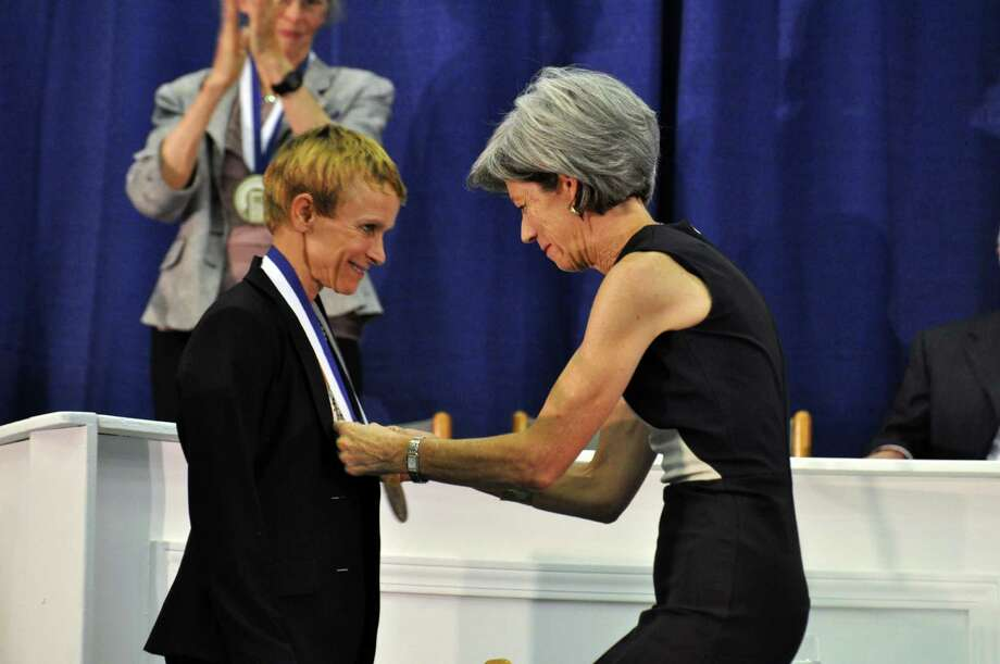 Julie Krone, the first female jockey to win a Triple Crown event, accepts her medal from Beth Quillen Thomas  during the induction ceremony for the National Women's Hall of Fame Saturday Oct. 12, 2013 at the New York Chiropractic College Athletic Center in Seneca Falls, N.Y. Photo: Susan Clark Porter, AP / Finger Lakes Times