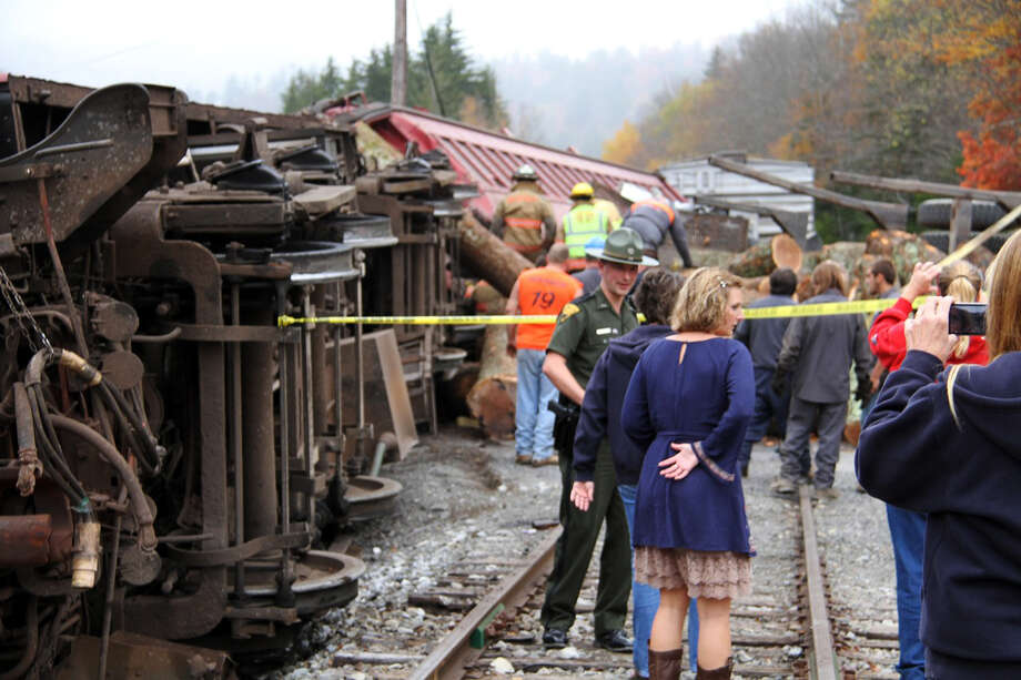 In this photo provided by the Pocahontas Times, crews work at the site where a truck carrying logs down Cheat Mountain on U.S. Route 250 crashed into the side of a train taking passengers on a scenic tour in rural Randolph County, W.Va., on Friday, Oct. 11, 2013. The crash killed one person and injured more than 60 others, according to emergency services officials. Photo: Geoff Hamill, AP / The Pocahontas Times