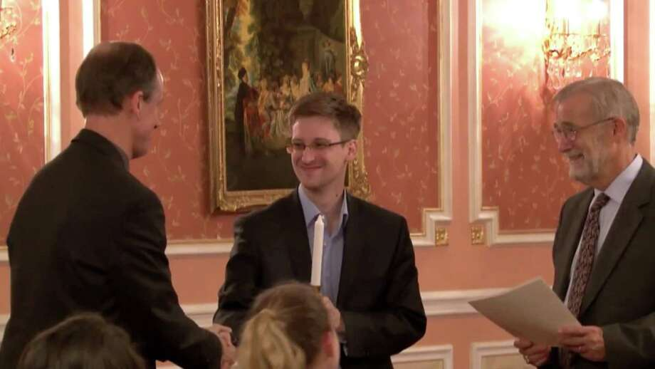 In this image made from video released by WikiLeaks on Friday, Oct. 11, 2013, former National Security Agency systems analyst Edward Snowden, center, receives the Sam Adams Award in Moscow, Russia. Snowden was awarded the Sam Adams Award, according to videos released by the organization WikiLeaks. The award ceremony was attended by three previous recipients. Snowden, who is charged by a U.S. court with violating the Espionage Act for disclosing the classified NSA programs, has been granted asylum in Russia. At right is Raymond McGovern, a former U.S. government official, at left is former NSA executive Thomas Drake. Photo: Uncredited, AP / AP2013