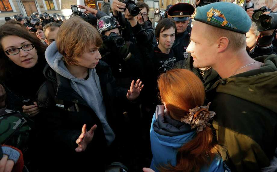 "A gay rights demonstrator, left, argues with anti-gay protesters during an authorized gay rights rally in St. Petersburg, Russia on Saturday, Oct. 12, 2013. The rally ended in scuffles after several dozen demonstrators were confronted by about 200 conservative and religious protesters. The city government had sanctioned the rally despite the Russian government's June passage of a contentious law outlawing gay ""propaganda."" Photo: Dmitry Lovetsky, AP / AP"