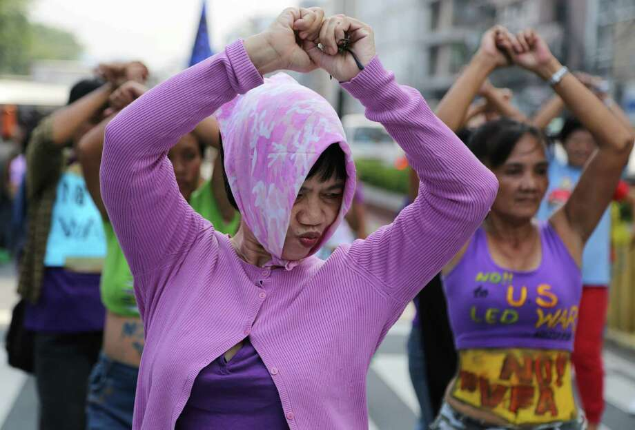 Filipino women dance during a protest near the U.S. Embassy in Manila, Philippines Thursday, Oct. 10, 2013. The group said the scheduled visit of U.S. State Secretary John Kerry was part of plans to increase U.S. military presence in the country. Kerry canceled the stop because of the threat posed by tropical storm Nari. Photo: Aaron Favila, AP / AP