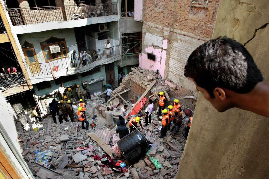 An Indian man watches rescue workers clean up debris of a collapsed building in New Delhi, India, Wednesday, Oct. 9, 2013. The three-story home that collapsed in India's capital was located in a crowded residential area of northern New Delhi, where narrow roads made rescue and cleanup efforts difficult. At least two people were killed in the collapse, according to local sources. Photo: Tsering Topgyal, AP / AP2013