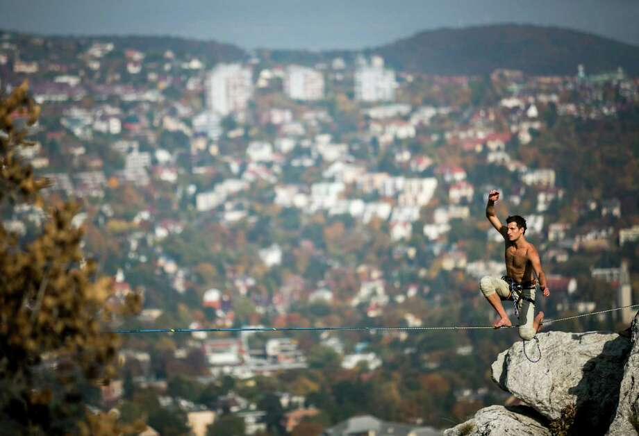 In this picture made available on Sunday, Oct. 13, 2013 a participant balances on a stretched belt during a slackline event organized by the Outdoor Inhales group at the Tunderszikla rock in Budapest, Hungary, Saturday, Oct. 12, 2013. Photo: Balazs Mohai, AP / MTI