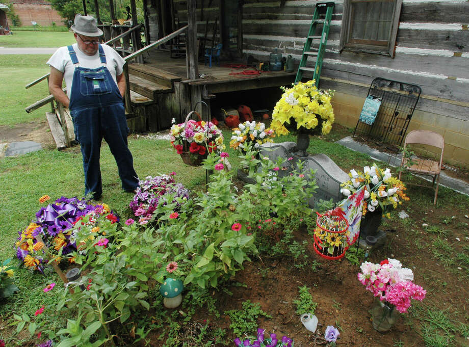 FILE - In this photo taken Aug. 10, 2012, James Davis, 73, stands over the grave of his wife, Patsy, in the front yard of the home they shared in Stevenson, Ala. A closely divided Alabama Supreme Court rejected the appeal of Davis on Friday, Oct. 11, 2013 who fought to keep his wife's grave in his front yard. In a 5-3 decision the state's high court rejected a request by Davis to take up his case after the Alabama Court of Civil Appeals ruled against him in April and in favor of the City of Stevenson. Photo: Jay Reeves, AP / AP