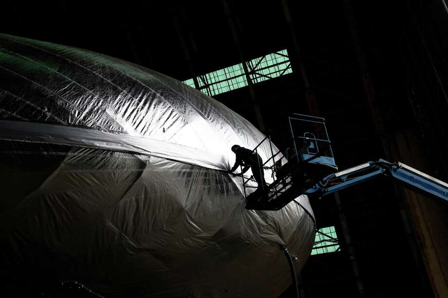 In this Jan. 24, 2013, file photo, Leonel Cruz works on the Aeroscraft airship, a high-tech prototype airship, in a World War II-era hangar in Tustin, Calif., A $35 million lighter-than-air dirigible was damaged and began leaking helium when part of the hangar roof collapsed Monday, Oct. 7, 2013 at a former Marine base in Southern California, authorities said. The partial collapse was reported just after 7:45 a.m. at one of the World War II-era blimp hangars on the grounds of the former Marine Corps Air Station in Tustin, said Capt. Steve Concialdi of the Orange County Fire Authority. Photo: Jae C. Hong, AP / AP
