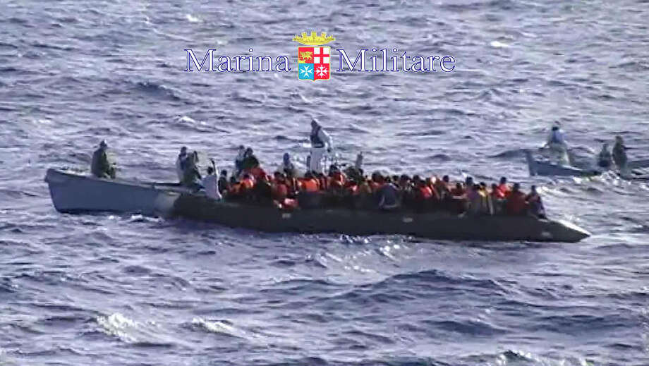 In this photo grabbed from a footage released by the Italian Navy Sunday, Oct. 13, 2013, migrants receive help from two raft from the Italian Navy ship Libra, off the Sicilian island of Lampedusa Saturday, Oct.12, 2013.  In recent days hundreds of migrants have drowned as smugglers' ship packed with migrants sank or capsized. The deaths have sharpened calls for a coordinated European response to the wave of asylum-seeker fleeing war and repression making their way to Libya to embark on a sea journey, mostly in rickety smugglers' boats en route to Italy's southernmost island of Lampedusa, just 70 kilometers (50 miles) away. Despite the perils, the boats keep coming. Authorities have rescued hundreds more at sea this weekend. Photo: AP / Italian Navy
