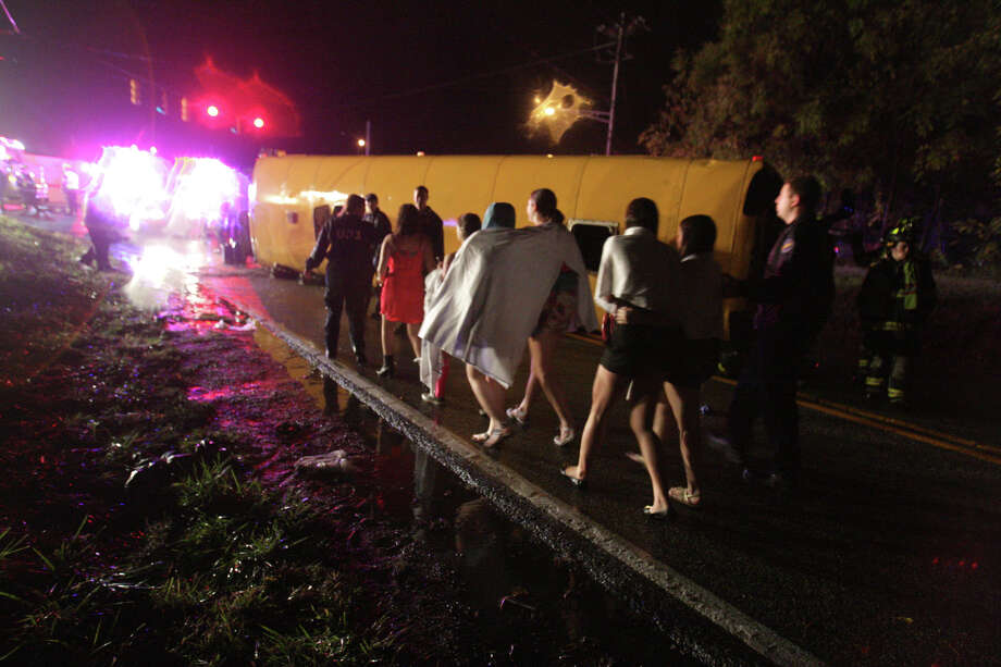 Passengers walk past a bus that overturned on Howell School Road after colliding with a car carrier truck, reported about 10:00 p.m. Thursday evening, Oct. 10, 2013. In a news release, state police Cpl. John Day says about 40 young adults, ages 18 to 22, were on the bus at the time. Photo: WILLIAM BRETZGER/THE NEWS JOURNAL, AP / AP2013