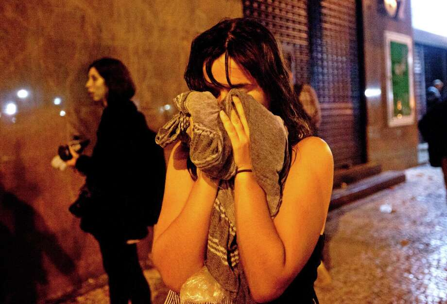 A woman covers from tear gas fired by police  near the Cinelandia square after a march in support of teachers on strike in Rio de Janeiro, Brazil, Monday, Oct. 7, 2013. Teachers have been on strike demanding better pay for almost two months. Photo: Silvia Izquierdo, AP / AP2013