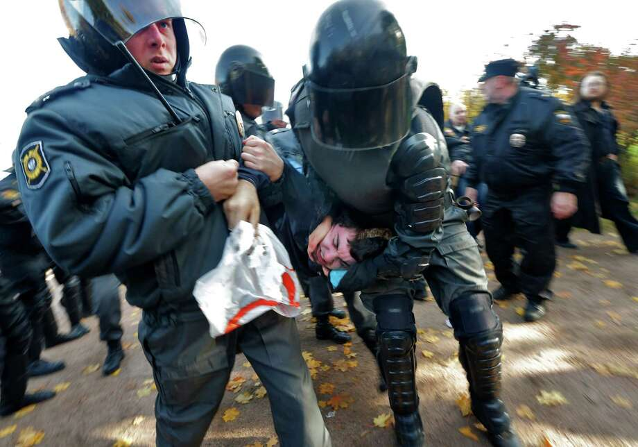 "Riot police detain an anti-gay protester during an authorized gay rights rally in St. Petersburg, Russia on Saturday, Oct. 12, 2013. The rally ended in scuffles after several dozen demonstrators were confronted by about 200 conservative and religious protesters. The city government had sanctioned the rally despite the Russian government's June passage of a contentious law outlawing gay ""propaganda."" Photo: Dmitry Lovetsky, AP / AP"