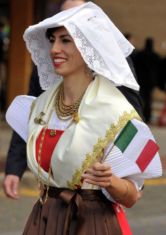 Lisa D'Acunto waves the Italian flag while walking in the parade during Columbus Day festivities in Stamford, Conn., on Sunday, Oct. 13, 2013. Photo: Jason Rearick / Stamford Advocate
