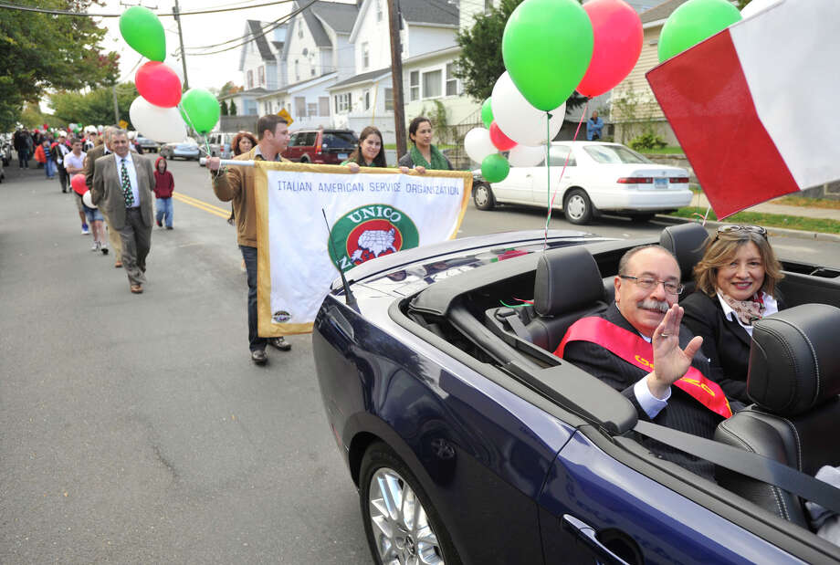 Parade Grand Marshall Luciano Sclafani Jr waves to pedestrians while seated next to his wife, Rosa, during the Columbus Day parade in Stamford, Conn., on Sunday, Oct. 13, 2013. Photo: Jason Rearick / Stamford Advocate