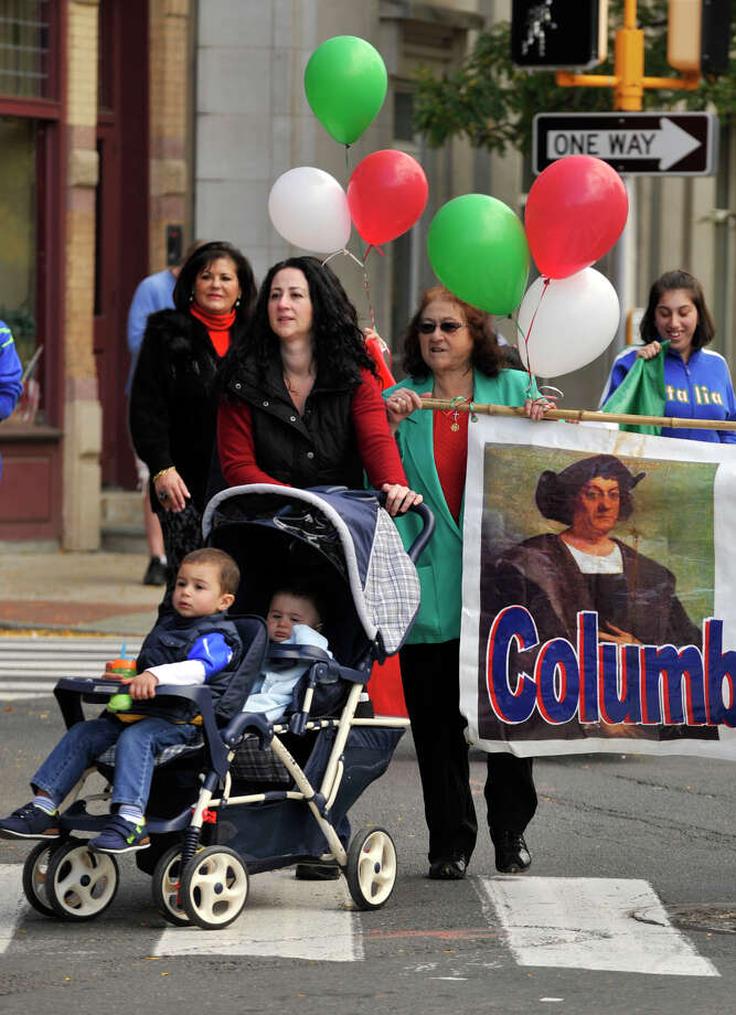 Rosanna Servidio pushes a stroller containing her sons Michael, front, and Peter while walking in the Columbus Day parade next to her mother, Teresa Mallozzi, in Stamford, Conn., on Sunday, Oct. 13, 2013. Photo: Jason Rearick / Stamford Advocate