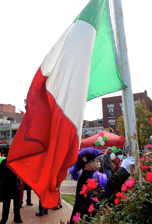 Giuseppe Pampena with the Knights of Columbus raises the Italian flag during Columbus Day festivities at Columbus Park in Stamford, Conn., on Sunday, Oct. 13, 2013. Photo: Jason Rearick / Stamford Advocate