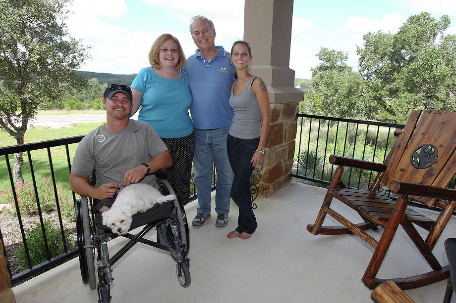 Wounded warrior Kyle Malin (left) and his wife, Alicia (far right) pose for a photograph with Helping a Hero's Dave Mulholland and his wife Katherine at Malin's home near Canyon Lake on Thursday, Oct. 10, 2013. Malin lost his legs while serving in Afghanistan three years ago. Through Helping a Hero, Malin and his family received the home designed to accommodate Malin's needs. Dave Mulholland is the South Texas Chairman of Helping a Hero and donated two additional plots of land in the same neighborhood as Malin to help other wounded soldiers. Photo: Kin Man Hui, San Antonio Express-News / ©2013 San Antonio Express-News