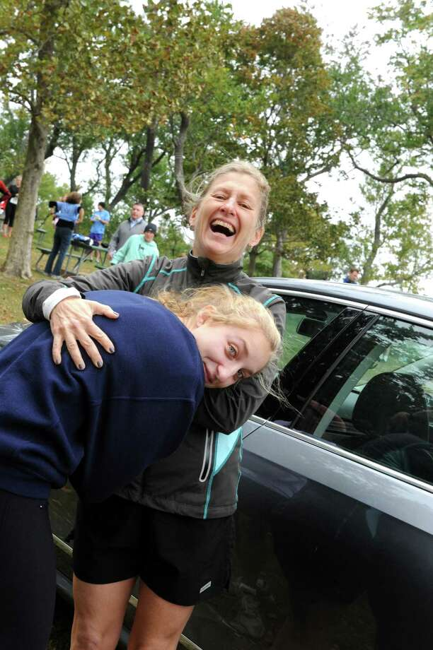 Maraja DiFazio, keeps her daughter warm, Katie, 17, of New Canaan, at 16th annual SusannahâÄôs Run at Greenwich Point Park, in Old Greenwich, Conn., Sunday, Oct. 14, 2013. Photo: Helen Neafsey / Greenwich Time