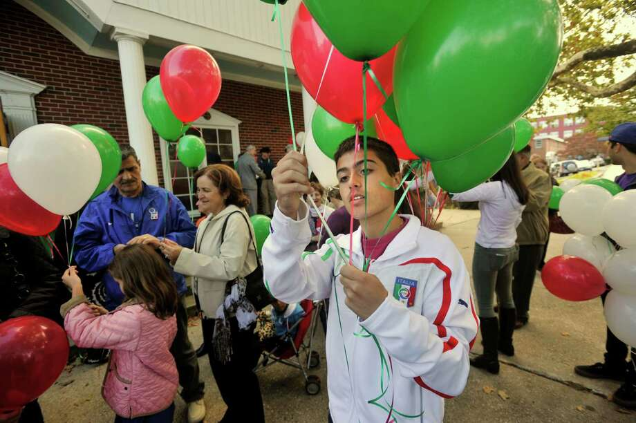 Bradley Cappello hands out balloons after Columbus Day mass outside Sacred Heart Church in Stamford, Conn., on Sunday, Oct. 13, 2013. Photo: Jason Rearick / Stamford Advocate