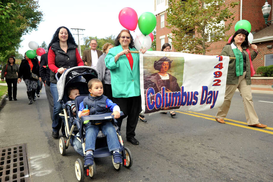 Stella Mallozzi, right, and her cousin Teresa Mallozzi carry a Columbus Day banner while walking with Teresa's daughter, Rosanna and her sons Michael, front, and Peter, in the Columbus Day parade in Stamford, Conn., on Sunday, Oct. 13, 2013. Photo: Jason Rearick / Stamford Advocate