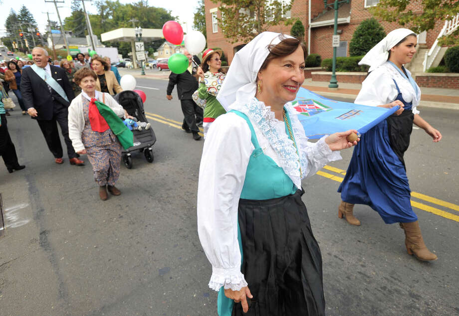 Rina Vitti, left, and Danielle Godejohn carry the Regione Lazio banner during Columbus Day parade in Stamford, Conn., on Sunday, Oct. 13, 2013. Photo: Jason Rearick / Stamford Advocate
