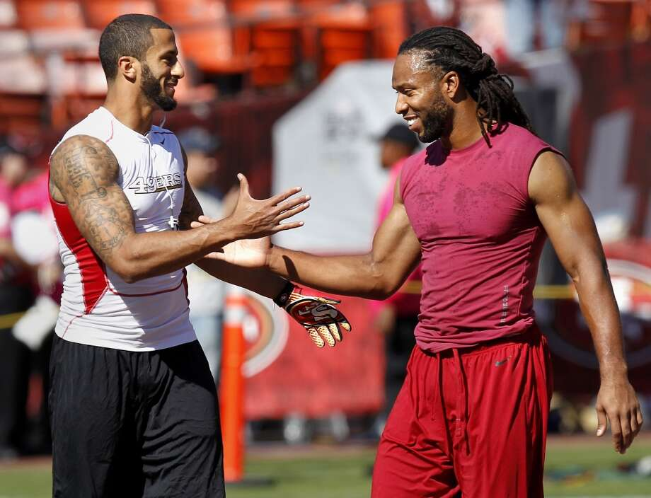 The 49ers quarterback Colin Kaepernick (left) greets the Cardinals wide receiver Larry Fitzgerald before the game Sunday October 13, 2013 in San Francisco, Calif. The San Francisco 49ers vs the Arizona Cardinals at Candlestick Park. Photo: Brant Ward, The Chronicle