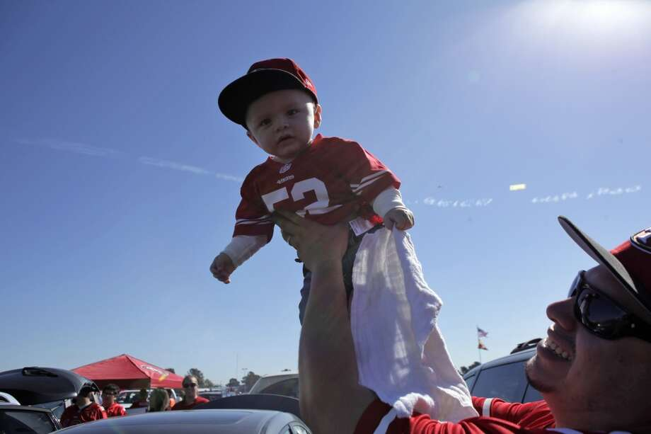 Sam Martinez holds his son Giovanni Martinez up in the parking lot as they tailgate before the San Francisco 49ers played the Arizona Cardinals at Candlestick Park in San Francisco, Calif., on Sunday, October 13, 2013. Photo: Carlos Avila Gonzalez, The Chronicle