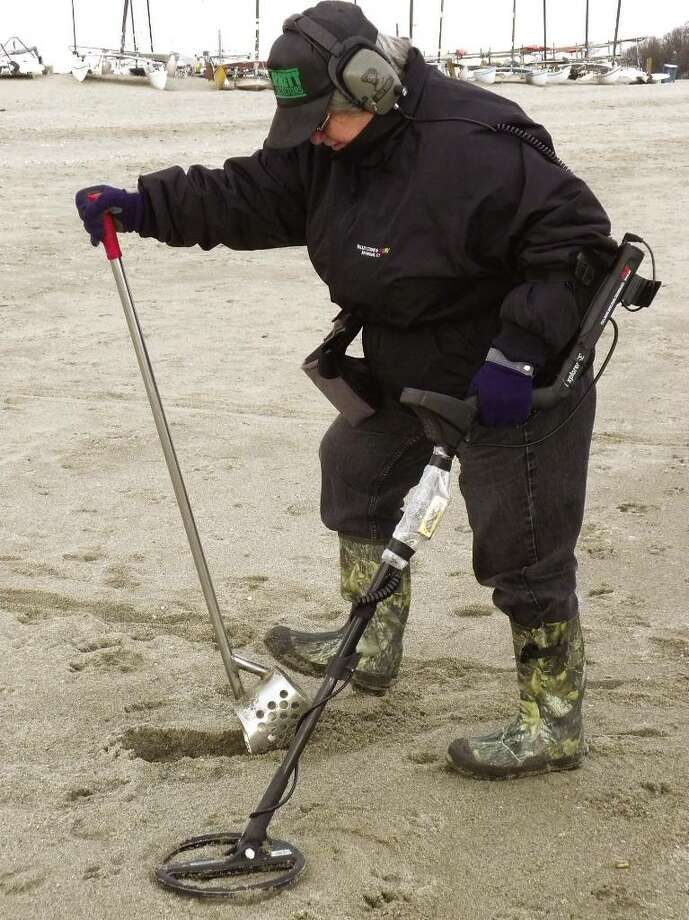 Carol Mayers of Oxford digs at the spot where her metal detector beeped on Tuesday at Jennings Beach in Fairfield. Photo: Gary Jeanfaivre / Fairfield Citizen
