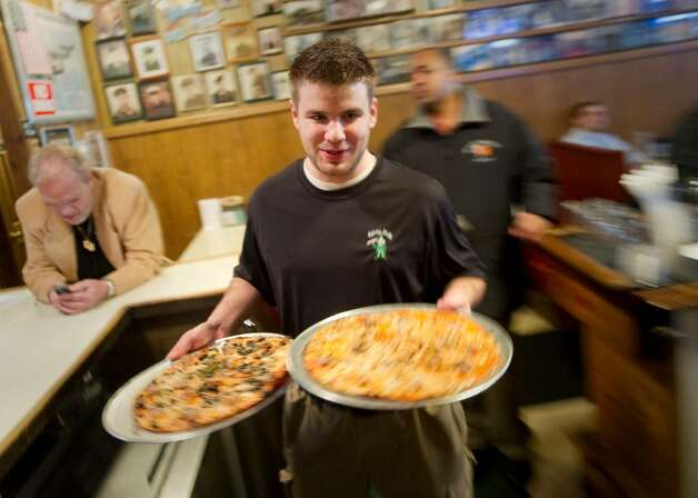 Mark Buckley serves up a couple of pies at Colony Grill in Stamford, Conn. on Thursday, Jan. 21, 2010. Photo: Chris Preovolos / Stamford Advocate