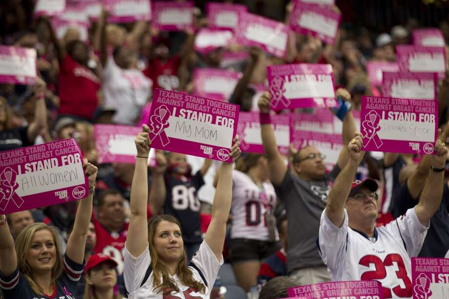 Fans hold up signs in support of breast cancer survivors during the second quarter. Photo: Brett Coomer, Houston Chronicle