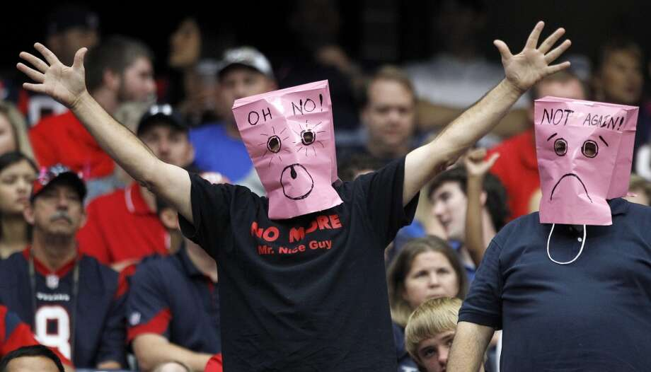 Fans wear pink bags on their heads while watching the loss. Photo: Brett Coomer, Houston Chronicle