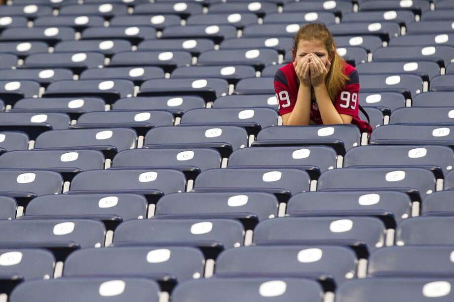 A fan sits alone after the loss. Photo: Brett Coomer, Houston Chronicle
